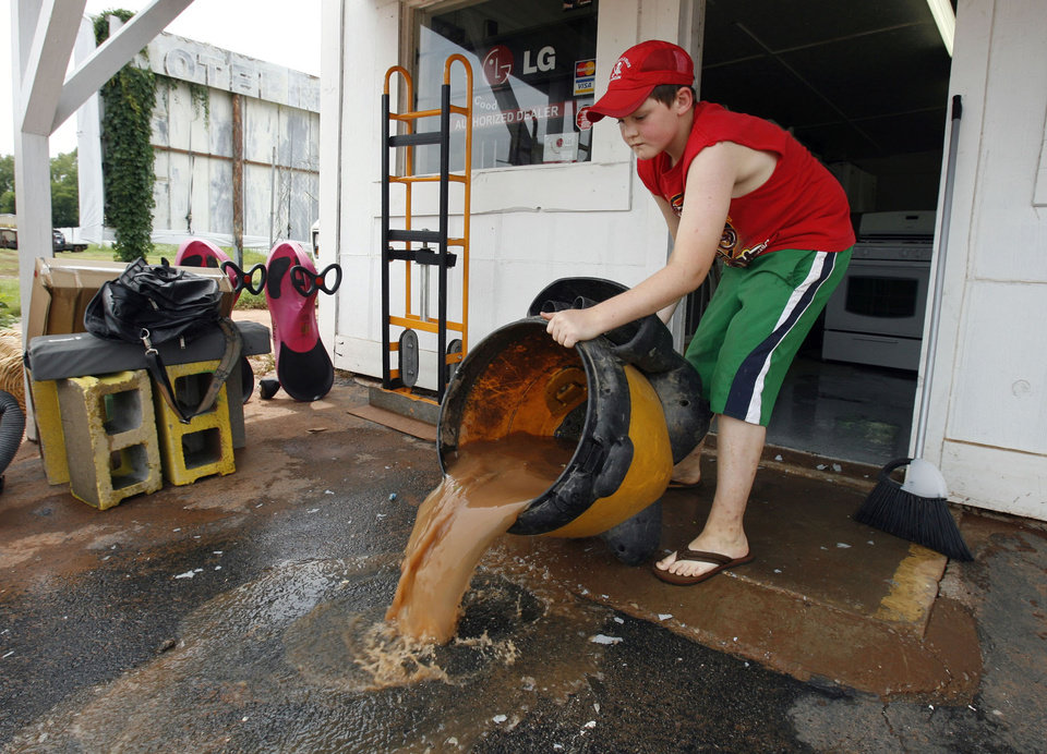 Photo - RAIN, FLOODS, FLOODING, FLOOD DAMAGE:  Jerrod Wingate dumps vacuumed creek water from the flroor of his uncle's store on Wednesday, July 11, 2007.   Walnut Creek flooded Tuesday covering the floor of  Justin Nimmo's Just in Time Appliance rental in Purcell, Oklahoma.    BY STEVE SISNEY, THE OKLAHOMAN ORG XMIT: kod