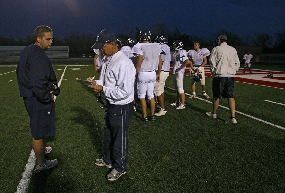 Photo - J.T. COBBLE: El Reno High School coach Tom Cobble, right, talks with his son J.T. as the El Reno football team practices at Yukon High School on Tuesday, Nov. 25, 2008, in Yukon, Okla. El Reno was getting some practice time on the artificial turf before playing this week's semifinal playoff game at Mustang High School.   STAFF PHOTO BY CHRIS LANDSBERGER  ORG XMIT: KOD
