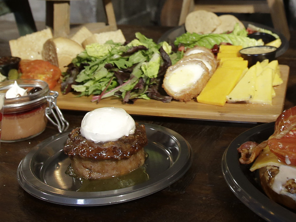 Photo - Sticky Toffee pudding, front center, is displayed along with the Ploughman's Platter, back, available at the Leaky Cauldron restaurant during a preview of Diagon Alley at the Wizarding World of Harry Potter at Universal Orlando, Thursday, June 19, 2014, in Orlando, Fla. (AP Photo/John Raoux)