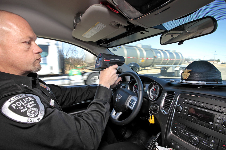 Photo - Kiowa Police Department Chief Tony Runyon uses a hand held radar to check the speed of a vehicle Friday on U.S.  69 in Kiowa. Photo by David McDaniel, The Oklahoman  David McDaniel