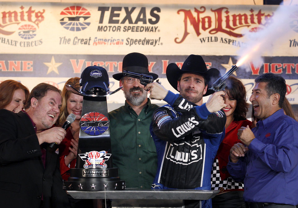 Photo -   Track President Eddie Gossage, left, ducks as Jimmie Johnson (48) fires blanks out of a revolver as he celebrates in victory lane following his win in the NASCAR Sprint Cup Series auto race at Texas Motor Speedway, Sunday, Nov. 4, 2012, in Fort Worth, Texas. (AP Photo/Tim Sharp)