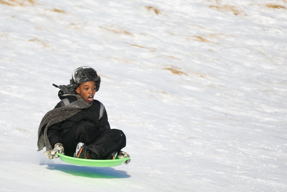 Photo - Dallas Todd, 11, rides down a hill in a saucer at Lake Harbor Park in of Norton Shores, Mich., Tuesday, Jan. 2, 2014. (AP Photo/The Muskegon Chronicle, Natalie Kolb) ALL LOCAL TV OUT; LOCAL TV INTERNET OUT