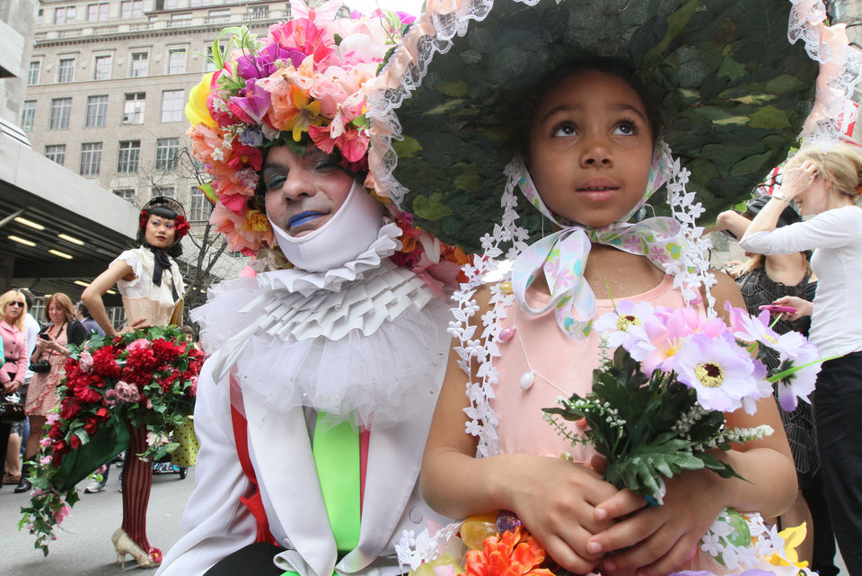 Photo -   Dinah King, 6, of the Queens borough of New York, foreground right, and a man calling himself Muffinhead, foreground left, pose for photographers as they take part in the Easter Parade along New York's Fifth Avenue Sunday April 24, 2011. (AP Photo/Tina Fineberg)