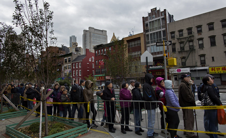 People wait on line for food, water and power for mobile devices at Confucius Plaza in the Chinatown neighborhood of New York, N.Y., Thursday, Nov. 1, 2012, in the wake of superstorm Sandy.  Hundreds of thousands in New York City alone were still without power Thursday, especially in Lower Manhattan, which remained in the dark roughly south of the Empire State Building after floodwaters had knocked out power.  (AP Photo/Craig Ruttle) ORG XMIT: NYCR107