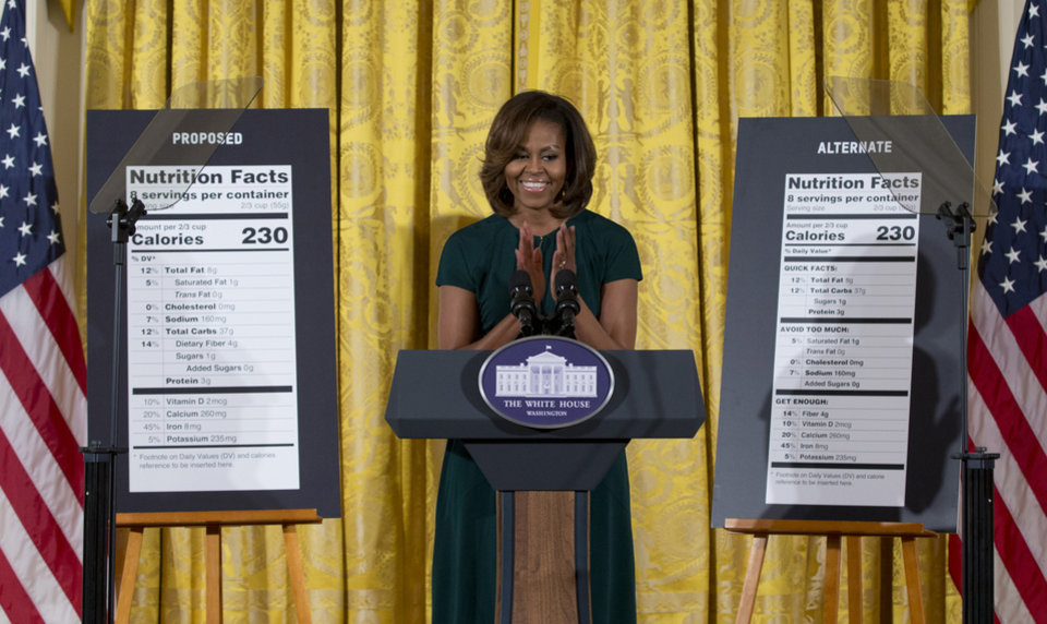 Photo - First lady Michelle Obama, flanked by enlargements of a proposed nutrition label, left, and a proposed alternate label, claps as she speaks during in the East Room of the White House in Washington, Thursday, Feb. 27, 2014, about helping parents and other consumers make healthier choices as part of her Let's Move program. The Obama administration is proposing new food labels that would make it easier to know about calories and added sugars, a reflection of the shifting science behind nutrition.  (AP Photo/Carolyn Kaster)