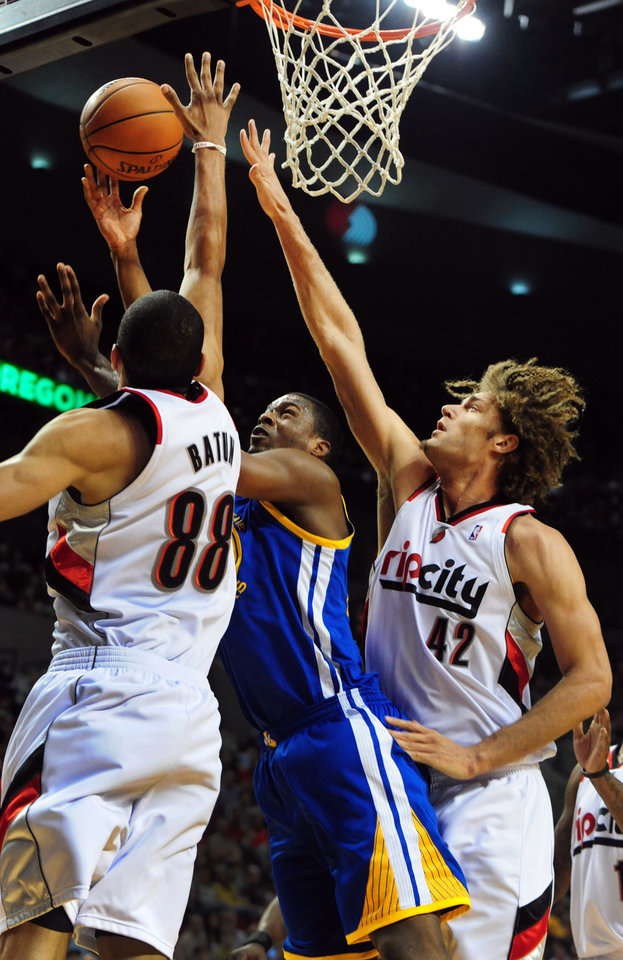 Photo - Golden State Warriors forward Harrison Barnes (40) has his shot blocked by Portland Trail Blazers forward Nicolas Batum (88) as Portland Trail Blazers center Robin Lopez (42) defends during the first half of an NBA basketball game in Portland, Ore., Sunday, April 13, 2014. (AP Photo/Steve Dykes)