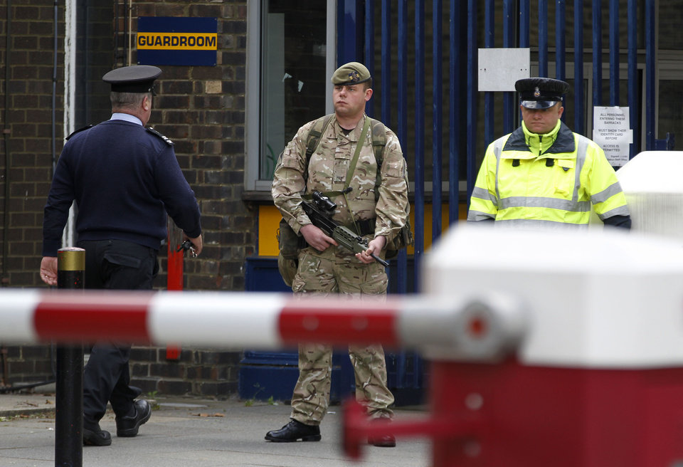 Photo - An armed soldier stands guard at the gate of the Royal Artillery Barracks near the scene of a terror attack in Woolwich, southeast London, Thursday, May 23, 2013. Police remained at the scene throughout the night after a brutal attack in a London street Wednesday, which left one member of the armed forces dead and two injured, and the two attackers were also hospitalised.  The British government Cabinet's emergency committee immediately called a meeting and Prime Minister David Cameron's office said security was stepped up at barracks across London. (AP Photo/Sang Tan)