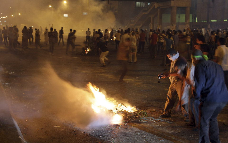 Photo - Supporters of Egypt's ousted President Mohammed Morsi block the street with burning tree during clashes with riot police at Nasr City, in Cairo, Egypt, Friday, July 26, 2013. Prosecutors opened an investigation of ousted President Mohammed Morsi on charges including murder and conspiracy with the Palestinian militant group Hamas, fueling tensions amid a showdown in the streets between tens of thousands of backers of the military and supporters calling for the Islamist leader's reinstatement. (AP Photo/Khalil Hamra)
