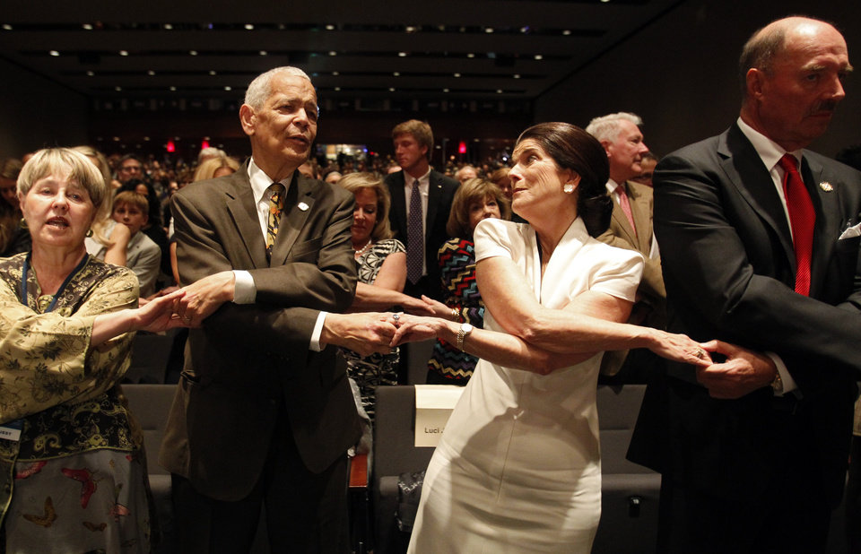 Photo - Social activist Julian Bond and Luci Baines Johnson hold hands as the crowd sings along