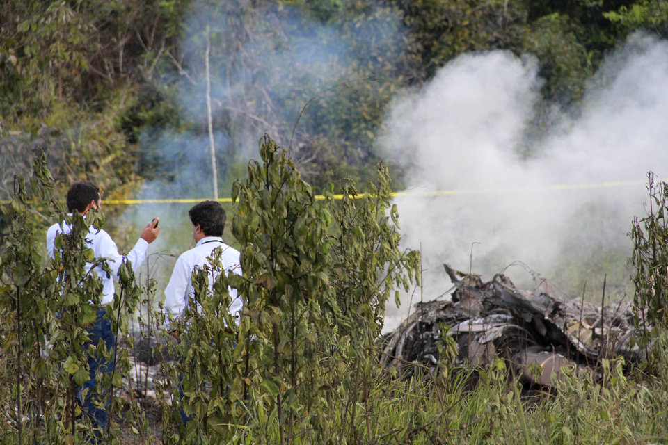 Investigators stand near the wreckage of a U.S.-owned cargo helicopter in Pucallpa, Peru, Monday, Jan. 7, 2013. Five U.S. citizens are among seven people killed in the crash in the Peruvian jungle. The heavy-lift, twin-rotor Chinook BH-234 chopper, owned by Columbia Helicopters in the Portland suburb of Aurora, Oregon, crashed Monday shortly after taking off from the provincial capital of Pucallpa bound for Tarapoto. (AP Photo/Noe Nole)