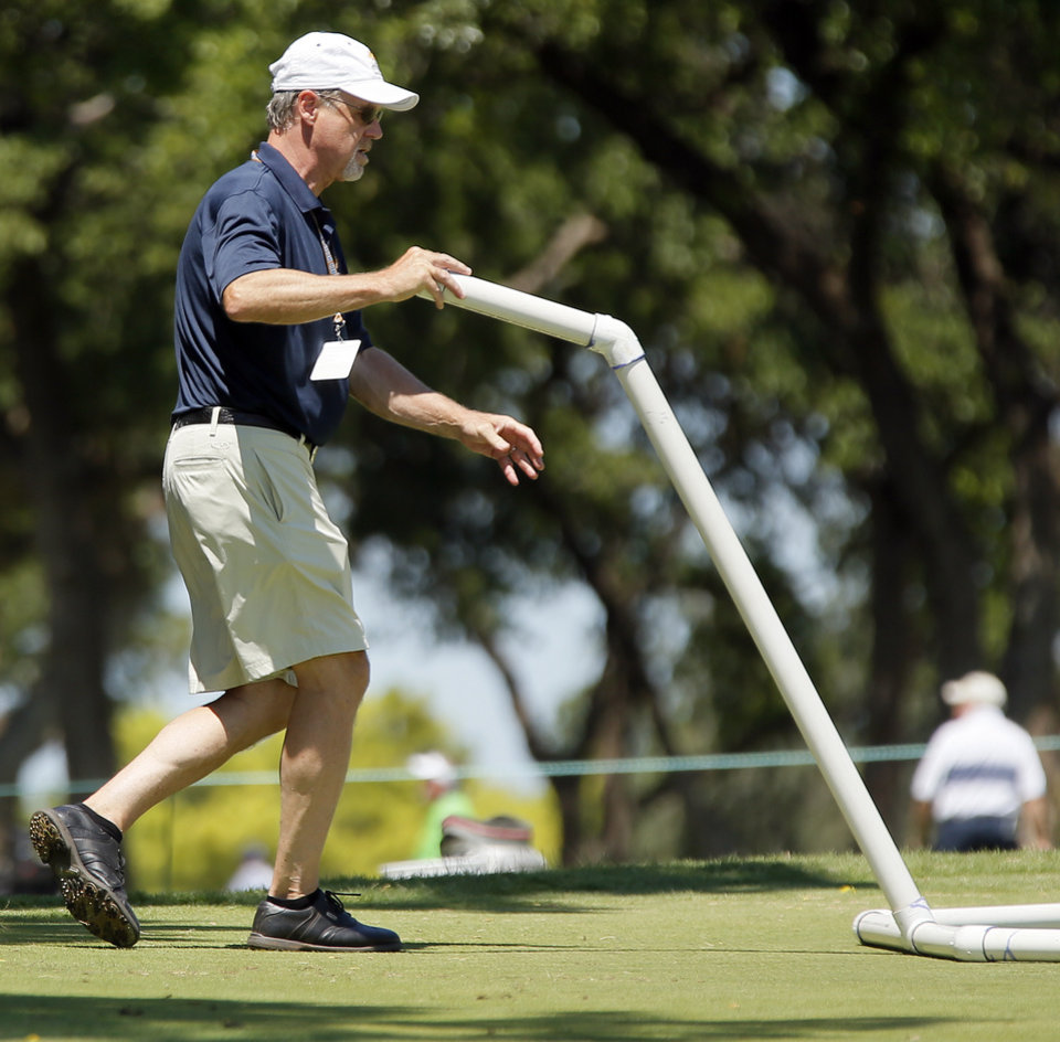 Photo - Volunteer Neil Helms clears golf balls off the practice green in chipping area during practice rounds for the U.S. Senior Open golf tournament at Oak Tree National in Edmond, Okla., Wednesday, July 9, 2014. Photo by Nate Billings, The Oklahoman