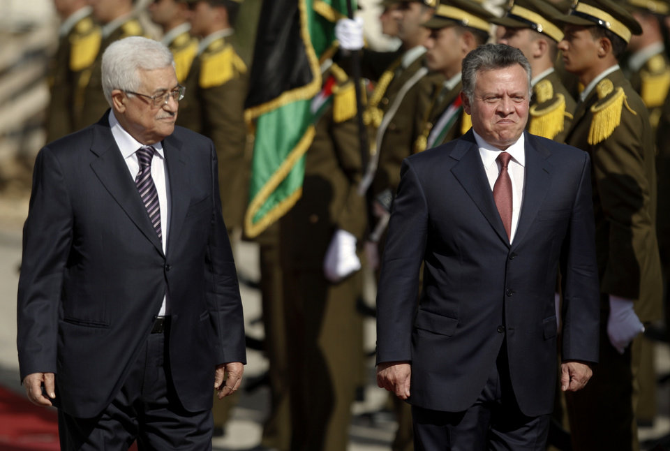 King Abdullah II of Jordan, right, and Palestinian President Mahmoud Abbas, walk past honor guards prior to their meeting in the West Bank city of Ramallah, Thursday, Dec. 6, 2012. Jordan�s King Abdullah II has begun a brief visit to the West Bank in support of Palestinian President Mahmoud Abbas� successful bid for U.N. recognition of a state of Palestine. (AP Photo/Majdi Mohammed)