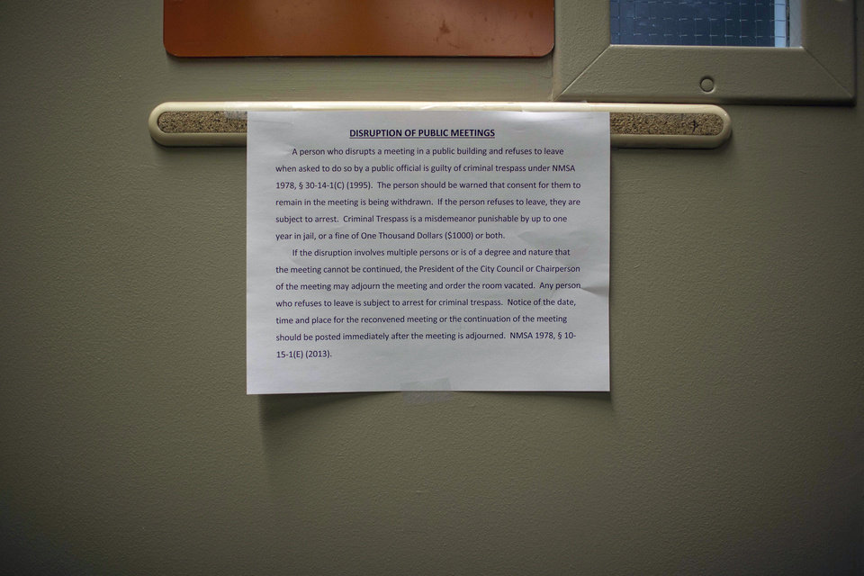Photo - A notice is posted on the door of city council chambers with