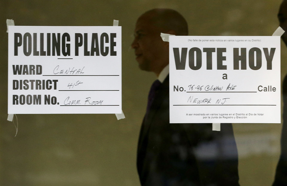 Photo - Newark Mayor Cory Booker, center, walks out of a polling place after casting his vote in a special election for the vacant New Jersey seat in the U.S. Senate, Wednesday, Oct. 16, 2013, in Newark, N.J. Booker is going up against Republican Steve Lonegan. (AP Photo/Julio Cortez)