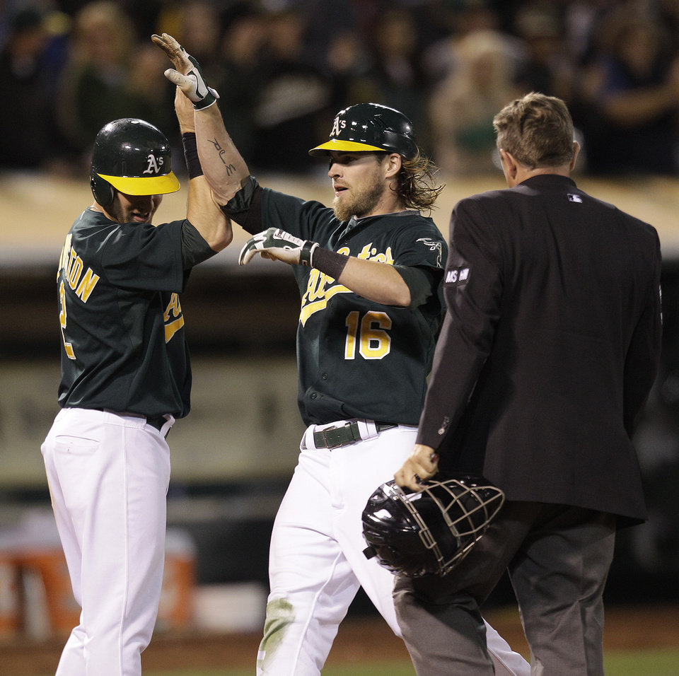 Photo -   Oakland Athletics' Josh Reddick, center, is congratulated after hitting a grand slam off Boston Red Sox's Mark Melancon in the seventh inning of a baseball game Friday, Aug. 31, 2012, in Oakland, Calif. (AP Photo/Ben Margot)