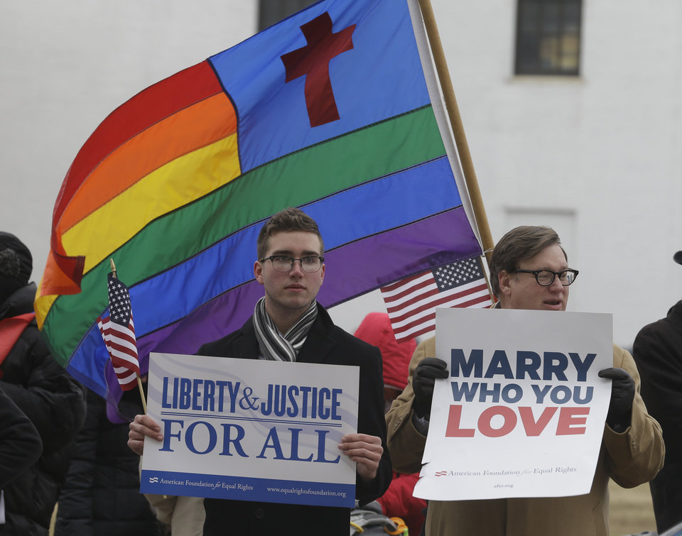 Photo - Spencer Geiger, left, of Virginia Beach, and Carl Johanson, of Norfolk, hold signs as they demonstrate outside  Federal Court  in Norfolk, Va., Tuesday, Feb. 4, 2014.  A federal judge heard arguments on whether Virginia's ban on gay marriage is unconstitutional. (AP Photo/Steve Helber)