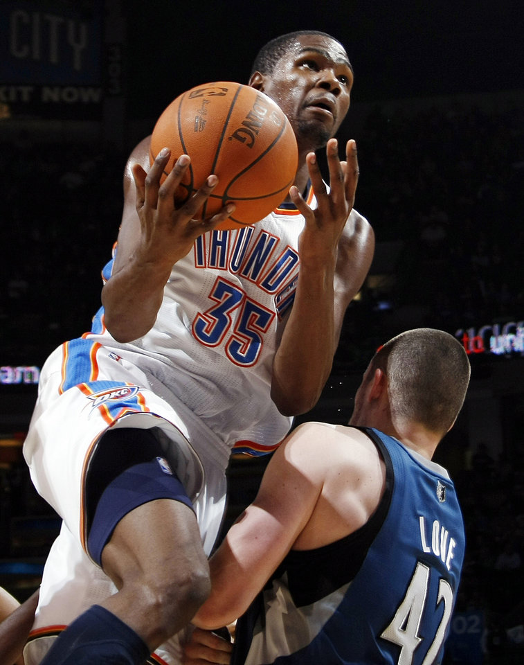 Photo - Oklahoma City's Kevin Durant (35) collides with Kevin Love (42) of Minnesota during the NBA basketball game between the Minnesota Timberwolves and the Oklahoma City Thunder at the Oklahoma City Arena, Monday, November 22, 2010, in Oklahoma City. Durant was called for an offensive foul on the play. The Thunder won, 117-107. Photo by Nate Billings, The Oklahoman