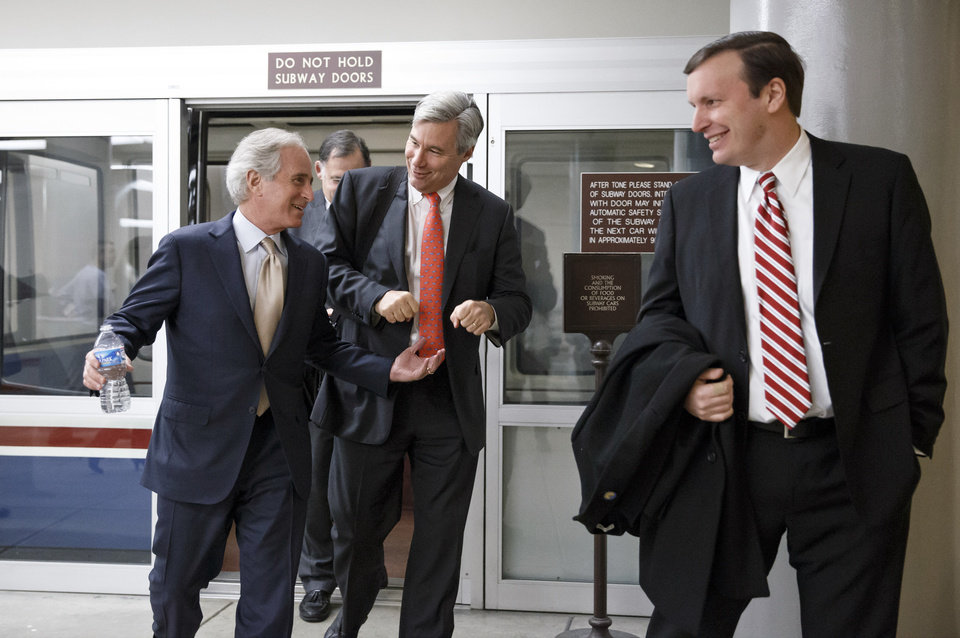 Photo - From left, Sen. Bob Corker, R-Tenn., Sen. Sheldon Whitehouse, D-R.I., and Sen. Chris Murphy, D-Conn., arrive for a procedural vote in the Senate on a bill that would extend unemployment benefits, at the Capitol in Washington, Monday, Jan. 6, 2014. Benefits expired for many long-term unemployed Americans on Dec. 28 after lawmakers did not extend the program as part of a bipartisan budget agreement. Sen. Jack Reed, D-R.I., is leading the effort to reauthorize the benefits for three months nationwide, but Republicans are balking however have balked at the proposed extension without offsets for the $6.5 billion that it will cost. (AP Photo/J. Scott Applewhite)