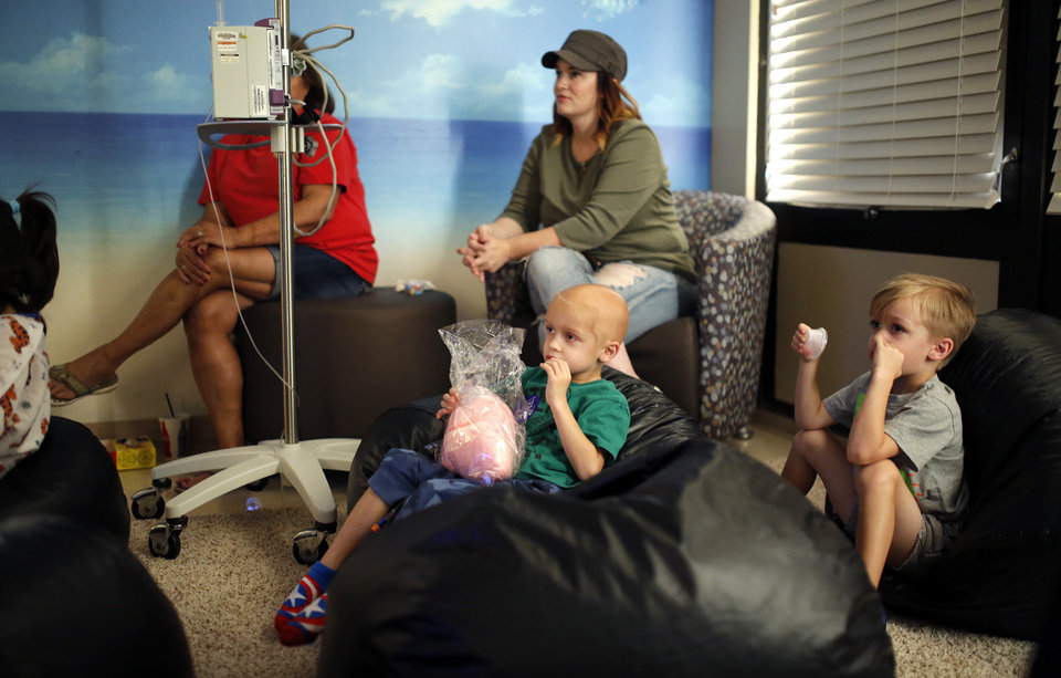 Photo -  McKoy Beard, 4, eats cotton candy as he watches a movie with his twin brother Sawyer Beard, at right, along with his mother, Christy Beard, and grandmother Karen Henneha at The Children's Hospital at OU Medical Center. 10 Strong, a group of mostly mothers of patients, raises money to hold events like movie night every few weeks on the 10th floor of the hospital. [Photo by Bryan Terry, The Oklahoman]