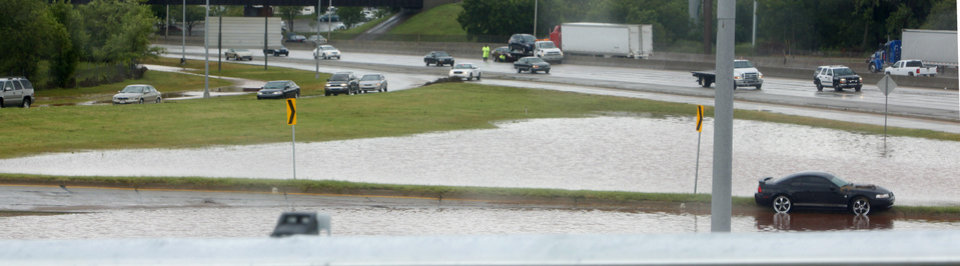 Photo - I-235 and I-44 interchange has become a lake with stranded vehicles after heavy rains as the Oklahoma Highway Patrol shuts down traffic east bound on I-44 in Oklahoma City Monday, June 14, 2010. Photo by Paul B. Southerland, The Oklahoman