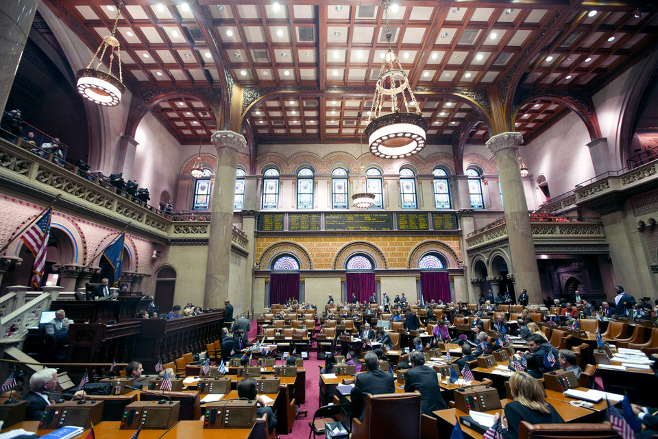 Photo - Legislators listen as members explain their vote on New York's Secure Ammunition and Firearms Enforcement Act in the Assembly Chamber at the Capitol on Tuesday, Jan. 15, 2013, in Albany, N.Y.  New York's Assembly passed the toughest gun control law in the nation and the first since the Newtown, Conn., school shooting, calling for a tougher assault weapons ban and provisions to try to keep guns out of the hands of the mentally ill who make threats. The measure passed, 104-43. (AP Photo/Mike Groll)