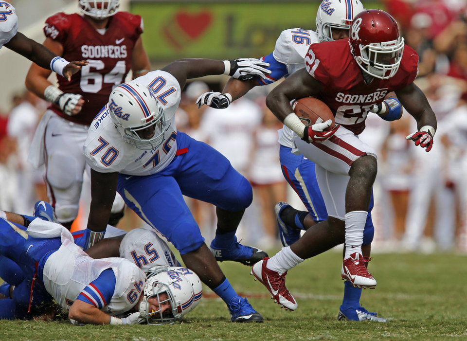 Photo - Oklahoma's Keith Ford (21) runs past Tulsa's Bradley White (49), Jerry Uwaezuoke (70), and Chris Hummingbird (46) during a college football game between the University of Oklahoma Sooners (OU) and the Tulsa Golden Hurricane at Gaylord Family-Oklahoma Memorial Stadium in Norman, Okla., on Saturday, Sept. 14, 2013. Oklahoma won 51-20. Photo by Bryan Terry, The Oklahoman