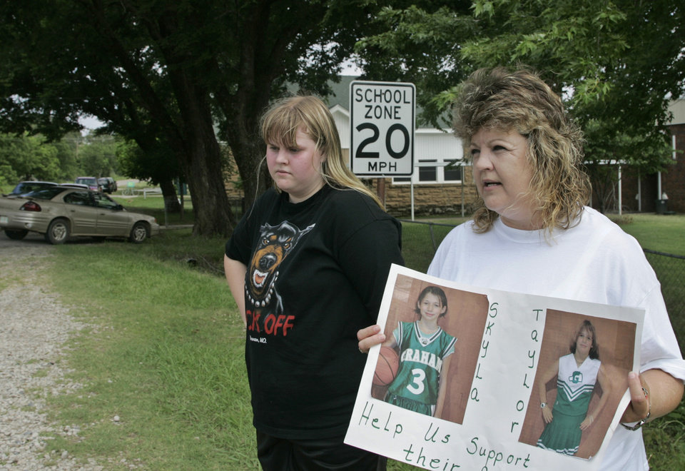 Photo - Dena Priddy, right, holds a sign with photos of the two Weeletka girls who were murdered Sunday, as she collects donations for the families outside Graham Public School in Weleetka, Okla., Tuesday, June 10, 2008. Her daughter, Tyler Couch, is at left. (AP Photo)