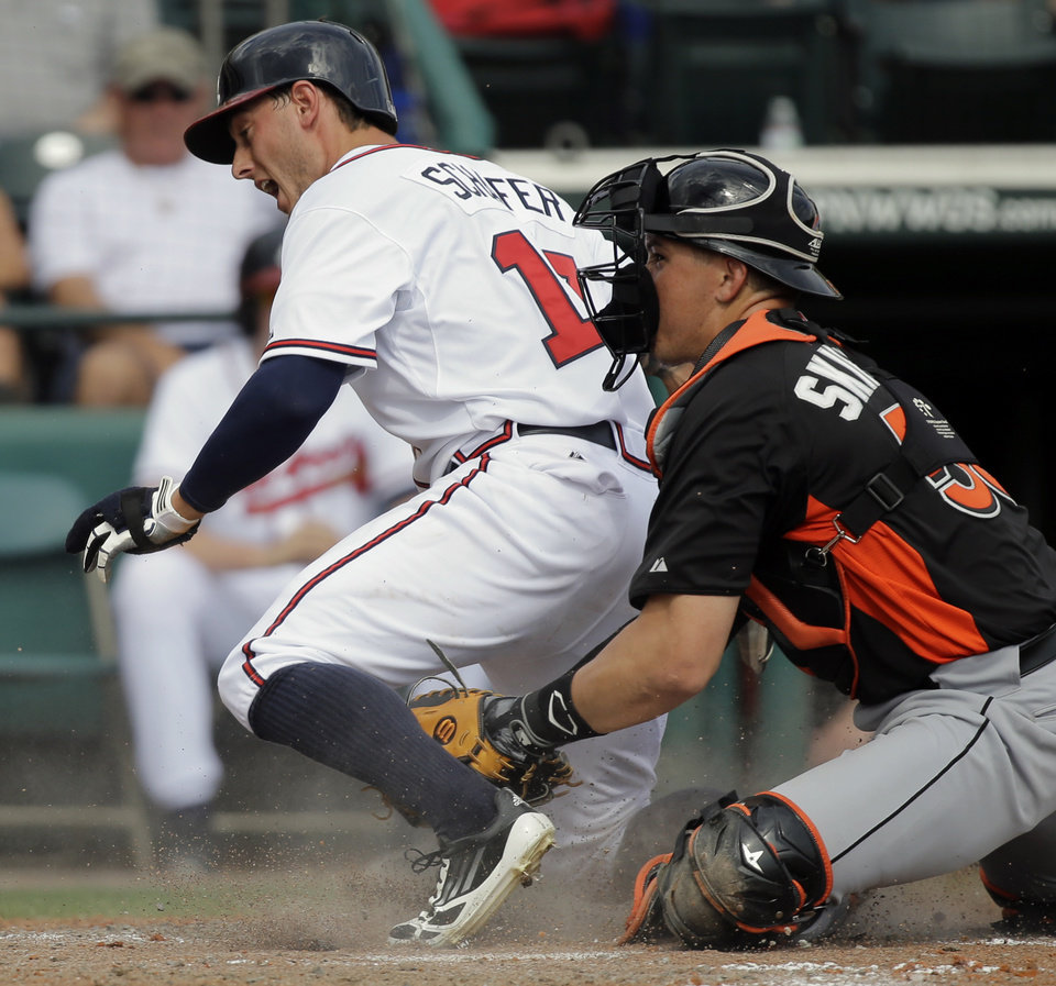 Photo - Atlanta Braves' Jordan Schafer (17) is tagged out by Miami Marlins catcher Kyle Skipworth, right, during the fifth inning of an exhibition spring training baseball game Monday, Feb. 25, 2013, in Kissimmee, Fla. (AP Photo/David J. Phillip)
