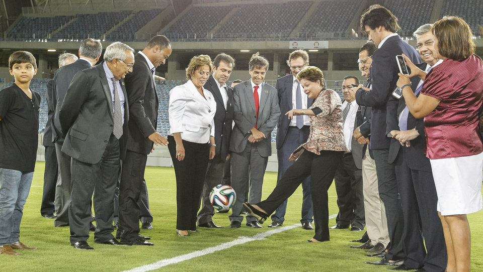 Photo - In this photo released by Brazil's Presidency, President Dilma Rousseff kicks a soccer ball during the inauguration of the Arena das Dunas soccer stadium in Natal, Brazil, Wednesday, Jan. 22, 2014. The event came a day after organizers admitted there is a serious risk the southern city of Curitiba might be dropped from the World Cup tournament because of lagging stadium construction. (AP Photo/Brazil's Presidency, Roberto Stuckert Filho)