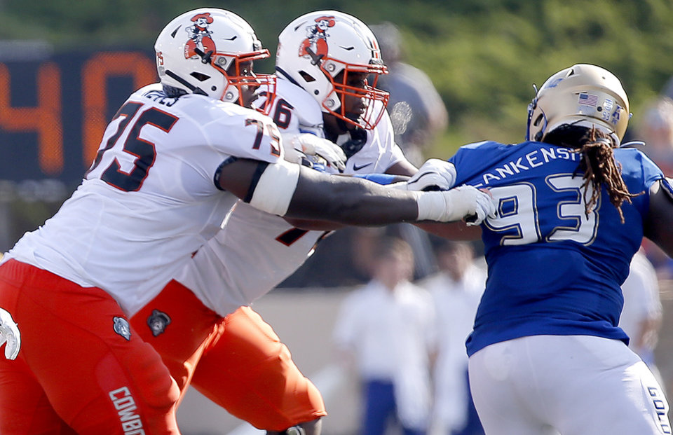 Photo - Oklahoma State's Marcus Keyes (75) and Dylan Galloway (76) block Tulsa's JaJuan Blankenship (93) during a college football game between the Oklahoma State University Cowboys (OSU) and the University of Tulsa Golden Hurricane (TU) at H.A. Chapman Stadium in Tulsa, Okla., Saturday, Sept. 14, 2019. [Sarah Phipps/The Oklahoman]
