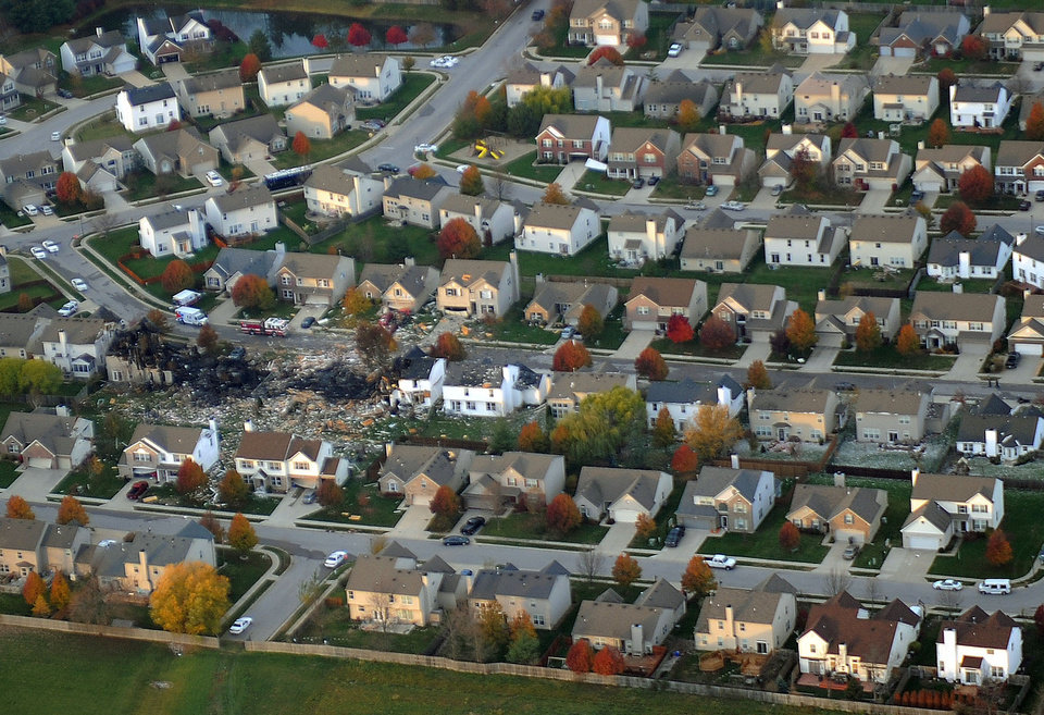 Photo -   This aerial photo shows the two homes that were leveled and the numerous neighboring homes that were damaged from a massive explosion that sparked a huge fire and killed two people, Sunday, Nov. 11, 2012, in Indianapolis. Nearly three dozen homes were damaged or destroyed, and seven people were taken to a hospital with injuries, authorities said Sunday. The powerful nighttime blast shattered windows, crumpled walls and could be felt at least three miles away. (AP Photo/The Indianapolis Star, Matt Kryger) NO SALES
