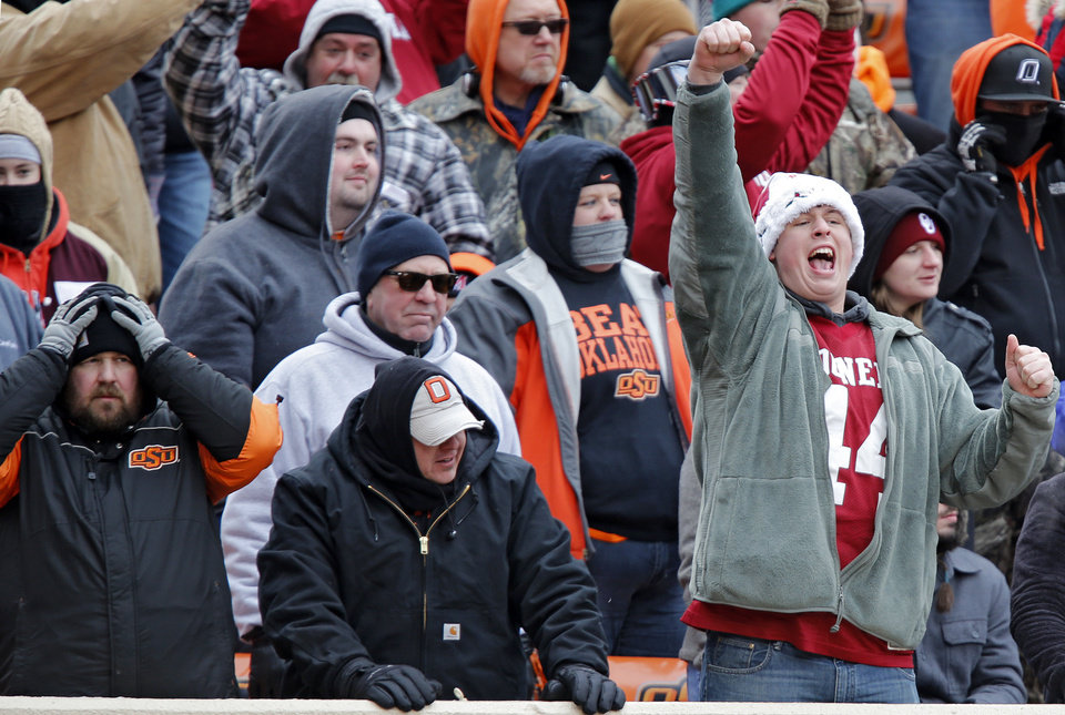 Photo - A Sooner fan celebrates a touchdown during the Bedlam college football game between the Oklahoma State University Cowboys (OSU) and the University of Oklahoma Sooners (OU) at Boone Pickens Stadium in Stillwater, Okla., Saturday, Dec. 7, 2013. Photo by Chris Landsberger, The Oklahoman
