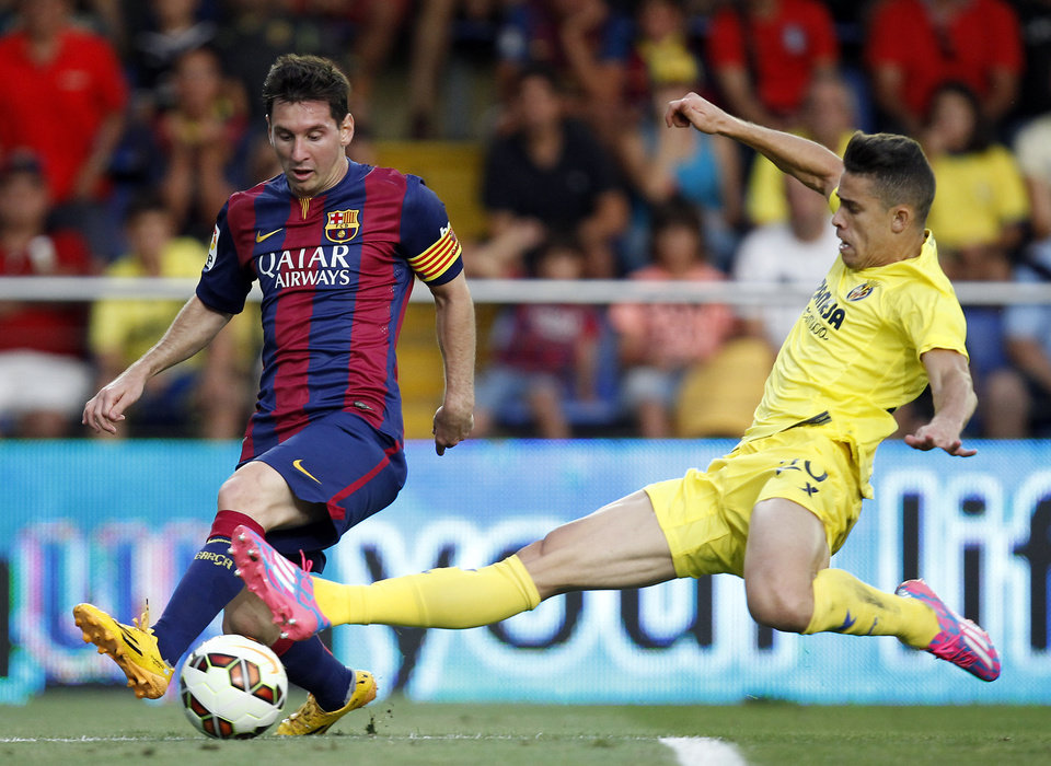 Photo - Barcelona's Lionel Messi, from Argentina, challenges for the ball with Villarreal's Grabiel Paulista from Brazil  during a Spanish La Liga soccer match at the Madrigal stadium in Villarreal, Spain, on Sunday, Aug 31, 2014.(AP Photo/Alberto Saiz)