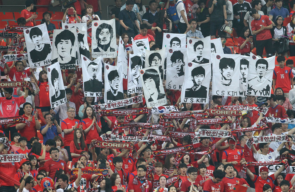 Photo - Soccer fans hold up portraits of South Korean national soccer team players before a friendly soccer match between South Korea and Tunisia at World Cup stadium in Seoul, South Korea, Wednesday, May 28, 2014. South Korea will play against Belgium, Russia and Algeria in Group H of the World Cup 2014 in Brazil. (AP Photo/Ahn Young-joon)