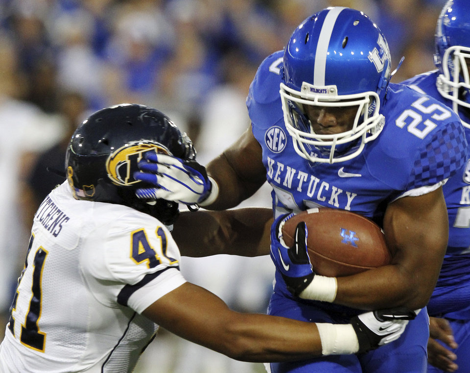 Photo -   Kentucky's Jonathan George (25) tries to shake a tackle from Kent State's Zack Hitchens during the first quarter of an NCAA college football game in Lexington, Ky., Saturday, Sept. 8, 2012. (AP Photo/James Crisp)