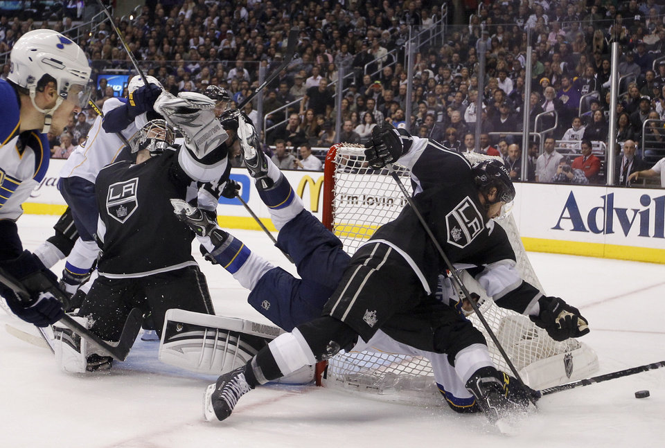 Photo - Los Angeles Kings' Mike Richards, top right, collides with St. Louis Blues' Jaden Schwartz as they fight for the puck during the third period in Game 6 of a first-round NHL hockey Stanley Cup playoff series in Los Angeles, Friday, May 10, 2013. The Kings won 2-1. (AP Photo/Jae C. Hong)
