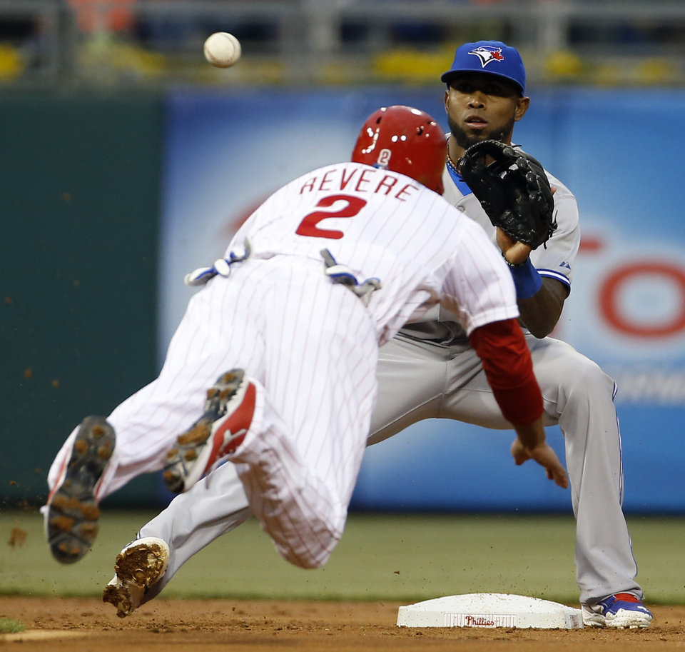 Photo - Philadelphia Phillies' Ben Revere, left, tries to steal second base as Toronto Blue Jays shortstop Jose Reyes waits on the throw during the first inning of an interleague baseball game, Monday, May 5, 2014, in Philadelphia. Revere was out on the play. (AP Photo/Matt Slocum)