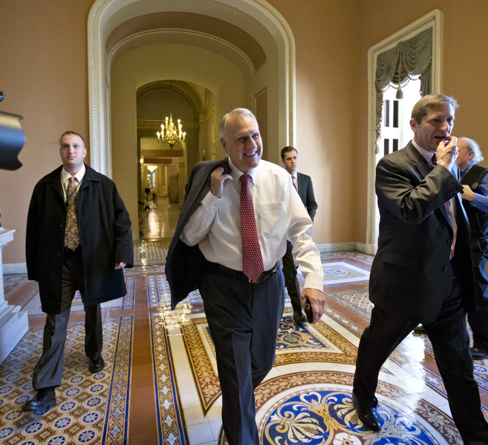 Photo - Senate Minority Whip Jon Kyl of Arizona walks between the Senate chamber and the office of Senate Minority Leader Mitch McConnell of Kentucky, as Democrats and Republicans try to negotiate a legislative path to avoid the so-called