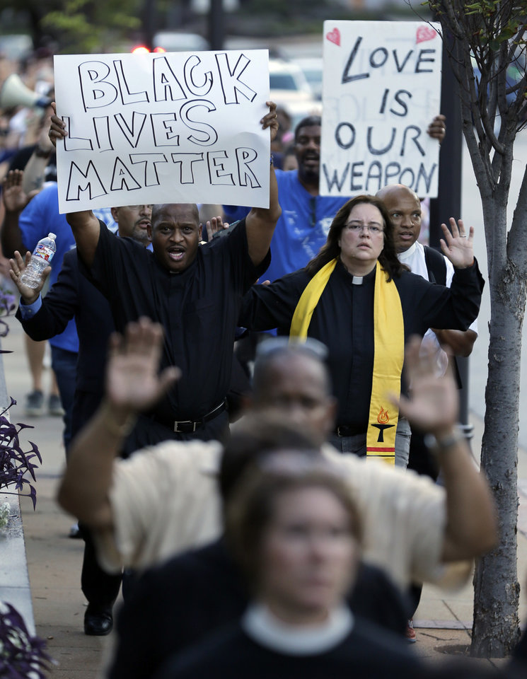 Photo - Protesters march to the Buzz Westfall Justice Center Wednesday, Aug. 20, 2014, in Clayton, Mo. A grand jury has begun hearing evidence as it weighs possible charges against the Ferguson police officer who fatally shot 18-year-old Michael Brown. (AP Photo/Jeff Roberson)