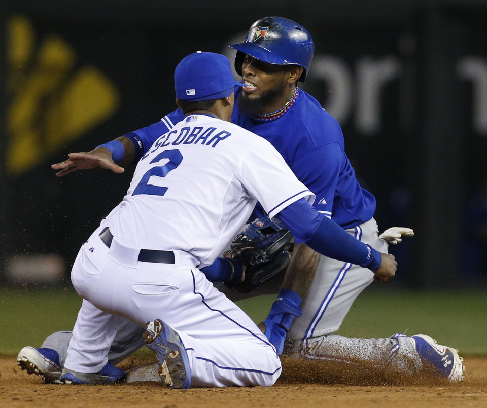 Toronto Blue Jays' Jose Reyes, back, injures his leg while beating the tag by Kansas City Royals shortstop Alcides Escobar (2) during the sixth inning of a baseball game at Kauffman Stadium in Kansas City, Mo., Friday, April 12, 2013. (AP Photo/Orlin Wagner)