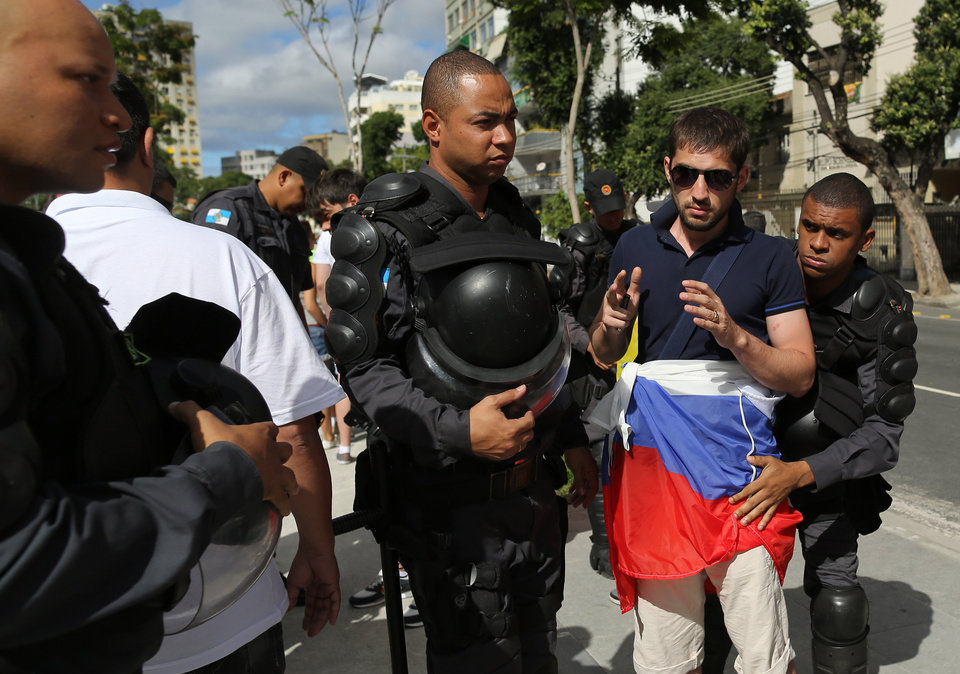 Photo - Riot policemen search a soccer fan wearing Russia's team colors as he arrives to Maracana stadium  for the group H World Cup match between Belgium and Russia, in Rio de Janeiro, Brazil, Sunday, June 22, 2014. (AP Photo/Leo Correa)