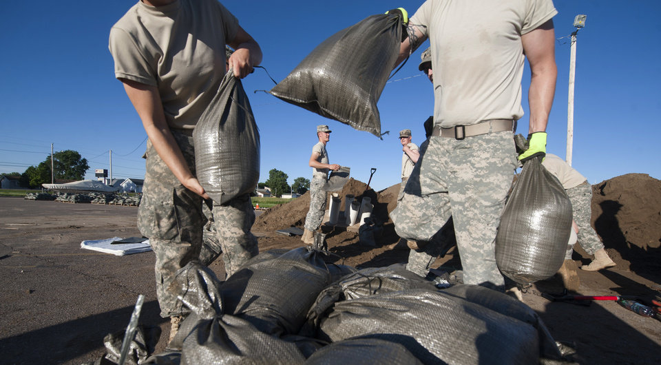 Photo - South Dakota National Guard troops fill sandbags in preparation for flooding along the Big Sioux River, Friday, June 20, 2014 in North Sioux City, S.D.The National Weather Service had predicted that the Big Sioux River would hit a record high around midday. But the service said Friday morning that the river crested at Sioux City, Iowa, around midnight a couple of feet below the previous record. (AP Photo/Dave Weaver)