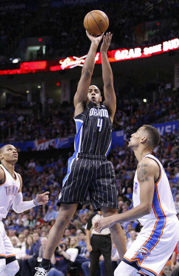 Photo - Orlando Magic guard Arron Afflalo (4) goes up for a basket between Oklahoma City Thunder's Russell Westbrook, left, and Thabo Sefolosha, right, during the first quarter of an NBA basketball game in Oklahoma City, Friday, March 15, 2013. (AP Photo/Alonzo Adams)