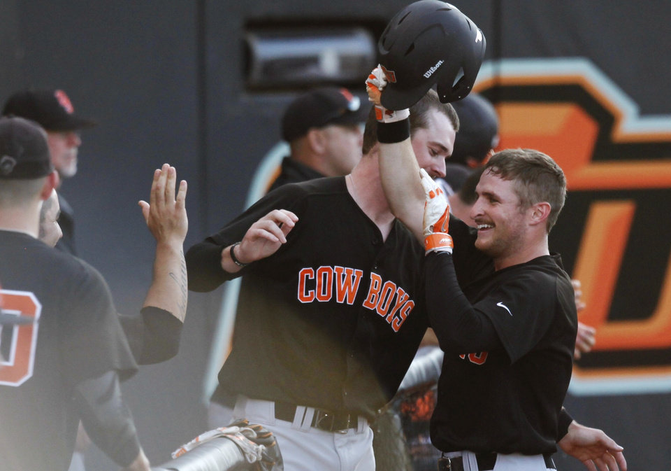 Oklahoma State base runner Saulyer Saxon (3) is congratulated after scoring a run during an NCAA Regional Baseball game between the Oklahoma State and Cal State Fullerton at Allie P. Reynolds stadium in Stillwater on May 31, 2014. Photo by KT King/The Oklahoman