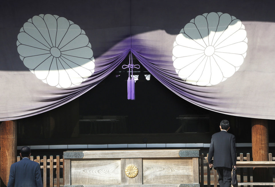 Photo - FILE - In this April 23, 2013 file photo, a group of Japanese lawmakers, seen silhouetted in the middle of the photo, offer prayers at Yasukuni Shrine in Tokyo during an annual spring festival. Justin Bieber has apologized to those he offended by visiting Japan's Yasukuni war shrine the week of April 20, saying he was misled to see it as only a place of prayer. The Shinto shrine in Tokyo honors 2.5 million war dead, including 14 convicted war criminals. China and South Korea in particular see Yasukuni as a symbol of Japan's past militarism and see visits to it as a lack of understanding or remorse over wartime history. (AP Photo/Koji Sasahara, File)