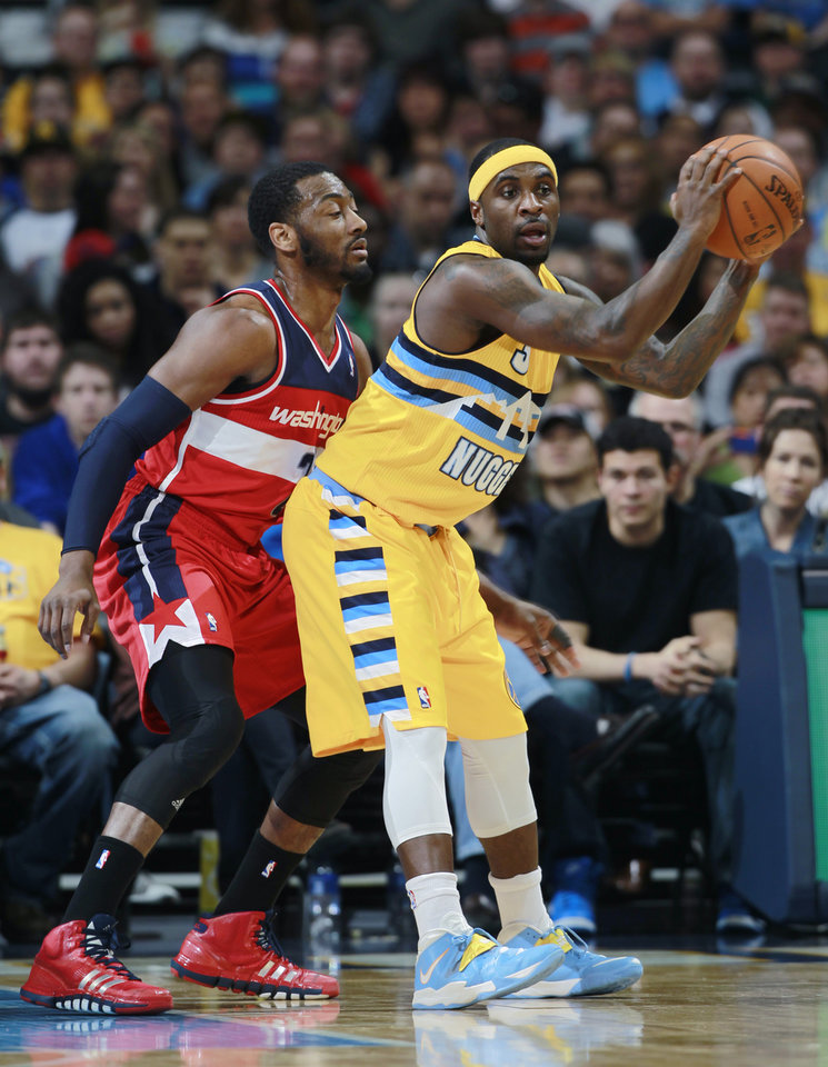 Photo - Washington Wizards guard John Wall, left, pressures Denver Nuggets guard Ty Lawson in the first quarter of an NBA basketball game, Sunday, March 23, 2014, in Denver. (AP Photo/David Zalubowski)