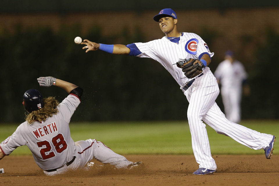 Photo - Chicago Cubs shortstop Starlin Castro, right, throws out Washington Nationals' Adam LaRoche at first base after forcing out Jayson Werth during the sixth inning of a baseball game in Chicago, Thursday, June 26, 2014. (AP Photo/Nam Y. Huh)