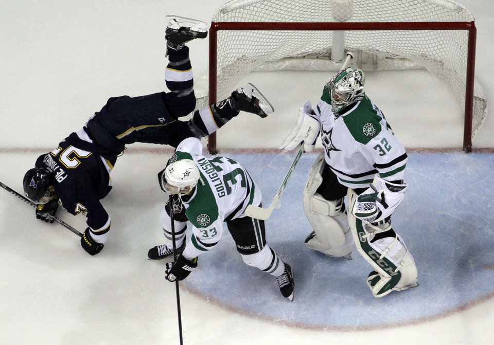 Photo - St. Louis Blues' Alex Pietrangelo, left, falls to the ice after flipping over Dallas Stars' Alex Goligoski, center, as Stars goalie Kari Lehtonen, of Finland, stands by during the second period of an NHL hockey game Saturday, March 29, 2014, in St. Louis. (AP Photo/Jeff Roberson)