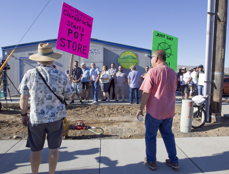 Photo - Dale Brown, left, and John Hultberg protest the opening of Altitude, a marijuana store as customers wait for the shop to open in Prosser, Wash., Tuesday, July 8, 2014. It was the first day marijuana could be sold legally in Washington state. Crawford, of Benton City, was purchasing the marijuana for recreational use. (AP Photo/Yakima Herald-Republic,  Gordon King)
