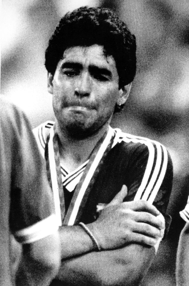Photo - FILE - The July 8, 1990 file photo shows Agentina's Diego Maradona, his arms crossed, fighting his tears back at the end of the Soccer World Cup final game in Rome, Italy, when Germany defeated Argentina 1-0. On Sunday, July 13, 2014, Germany and Argentina will face each other again in the final of the 2014 soccer World Cup.(AP-Photo/Kalle Tornstrom, file)